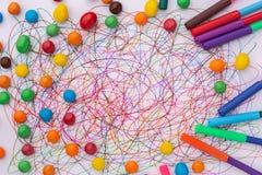 Kleurrijke vilten uiteindepen met snoepjes en gekrabbel op Witboek royalty-vrije stock fotografie