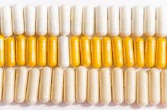 Kleurrijke vitaminen in capsules die op een rij liggen stock afbeeldingen