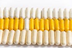 Kleurrijke vitaminen in capsules die op een rij liggen royalty-vrije stock foto's