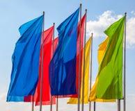 Kleurrijke vlaggen die over blauwe hemel golven Royalty-vrije Stock Afbeelding