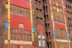 Kleurrijke voorgevel van oude verlaten industriële ruïne Verzegelde vensters, deuren Stock Afbeelding