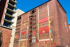 Kleurrijke voorgevel van oude verlaten industriële ruïne Verzegelde vensters, deuren Stock Foto