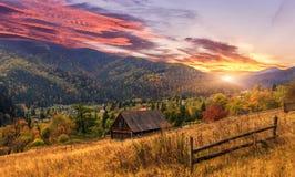 Kleurrijke warme zonsondergang over het berglandschap wolken op de hemel die in zonlicht gloeien Artistieke stijl stock foto's