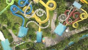 Kleurrijke waterdia in vermaak aquapark Lucht Mening Mensen die pret hebben die op dia's in openluchtwaterpark berijden bij stock video