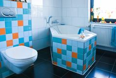Kleurrijke witte en blauwe badkamers met zwarte vloer Stock Foto