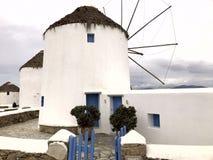 Kleurrijke witte voorgevel van een witte antieke molen met blauwe deuren tegen de hemel op het Eiland Mykonos stock foto