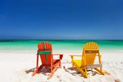 Kleurrijke zitkamerstoelen bij Caraïbisch strand Stock Foto's