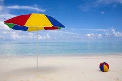 kleurrijke zonnescherm en bal bij het strand Stock Afbeeldingen