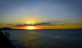 Kleurrijke Zonsondergang en sommige Wolken op Blauwe Hemel over Overzees Royalty-vrije Stock Afbeeldingen
