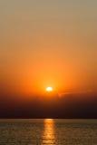 Kleurrijke zonsondergang in het overzees met bezinningen en wolken stock foto's