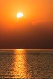 Kleurrijke zonsondergang in het overzees met bezinningen en wolken Stock Foto