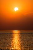 Kleurrijke zonsondergang in het overzees met bezinningen en wolken stock fotografie