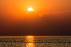 Kleurrijke zonsondergang in het overzees met bezinningen en wolken Royalty-vrije Stock Foto