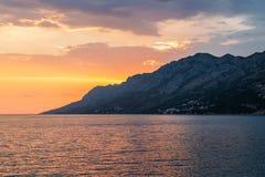 Kleurrijke zonsondergang over de berg op het Adriatische Overzees in Brela, Kroatië Stock Fotografie