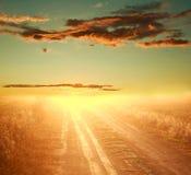 Kleurrijke zonsondergang over landweg op dramatische hemel Royalty-vrije Stock Afbeeldingen