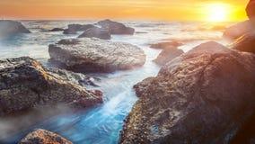 Kleurrijke zonsondergang over oceaan met grote stenenclose-up stock footage
