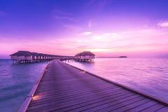 Kleurrijke zonsondergang over oceaan op de Maldiven Het eilandzonsondergang van de Maldiven De toevlucht van waterbungalowwen bij stock afbeelding