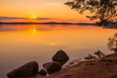 Kleurrijke zonsondergangavond bij meerkust stock afbeeldingen