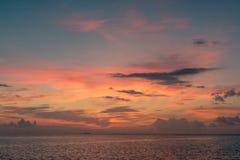Kleurrijke zonsondergangbezinning over een bewolkte hemel en een overzees royalty-vrije stock afbeelding
