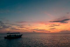 Kleurrijke zonsondergangbezinning over een bewolkte hemel en een overzees weinig boot op de oceaan stock foto's