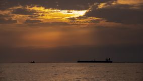 Kleurrijke zonsonderganghemel in de wolken op het overzees met silhouetten van schepen stock afbeelding