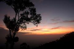 Kleurrijke zonsonderganghemel over het bos in Nan, Thailand stock foto