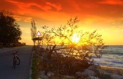 Kleurrijke zonsopgang, weg en fiets op de kust Stock Afbeelding