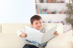 Kleuter die een boek op de laag in het kinderdagverblijf lezen royalty-vrije stock afbeelding