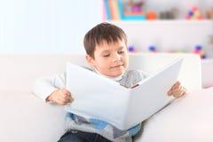 Kleuter die een boek op de laag in het kinderdagverblijf lezen royalty-vrije stock foto's
