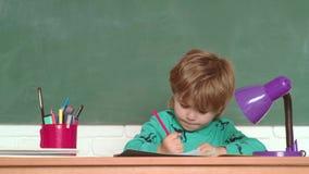 Kleuter, schoolkind Jonge geitjesschool Vrolijk glimlachend kind bij het bord Terug naar school en gelukkige tijd Terug naar stock videobeelden