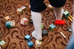 Kleuterjong geitje het spelen met kleurrijke houten blokken Onderwijsspeelgoed in kleuterschool die op de vloer wordt verspreid stock afbeelding