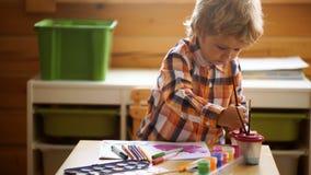Kleuterjongen die pret met kleurrijke verf hebben bij een opvang De creatieve tekening van de jong geitjepeuter thuis De kinderen stock videobeelden