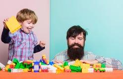 kleuterschool Gelukkige familievrije tijd Kindontwikkeling de bouwhuis met aannemer vader en zoonsspelspel klein stock afbeelding