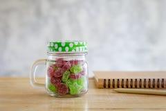 Kleverig suikergoed in een glaskruik op houten lijst met grijze achtergrond Stock Afbeelding