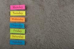 kleverige nota met dagen van week op grijze cementachtergrond Maandag, Dinsdag, Woensdag, Donderdag, Vrijdag, Zaterdag, en Zondag stock foto's