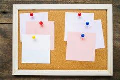Kleverige nota over cork raad op houten muurachtergrond, lege ruimte Stock Afbeeldingen