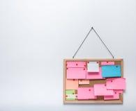 Kleverige nota's bij het hangen van cork bulletin Stock Foto