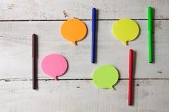 Kleverige nota's met gekleurde tellers op houten hoogste-mening als achtergrond Stock Foto