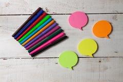 Kleverige nota's met gekleurde tellers op houten hoogste-mening als achtergrond Stock Afbeelding
