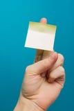 Kleverige nota, vinger omhoog van duim, gele herinnering op blauwe achtergrond Royalty-vrije Stock Foto