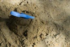 Klibba en skyffel i en hög av sand royaltyfri bild