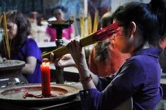 Klibbar be och brännande rökelse för asiatiskt folk i en pagod Arkivfoto