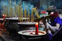 Klibbar be och brännande rökelse för asiatiskt folk i en pagod Royaltyfria Foton