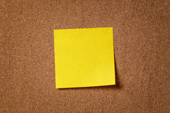 Klibbig anmärkning för gul påminnelse på korkbräde Arkivfoto