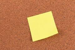 Klibbig anmärkning för gul påminnelse på korkbräde Royaltyfria Bilder