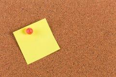 Klibbig anmärkning för gul påminnelse på korkbräde Arkivbild