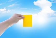 Klibbig anmärkning på manhanden med himmel- och molnbakgrund royaltyfri bild
