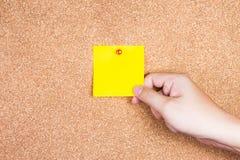 Klibbig anmärkning för gul påminnelse på korkbräde med handinnehavet Arkivbild