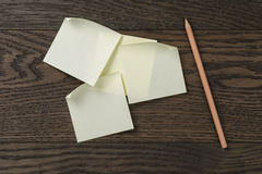 Klibbig anmärkningspåminnelse på tabellen för ekträ med blyertspennan Arkivfoto