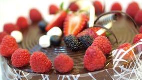Klibbig chokladkaka med nya jordgubbar och bär arkivfilmer